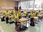 Kuvassa iloiset, liivinsä saaneet ekaluokkalaiset. Takana klubipresidentti Pekka Mänttäri ja opettaja Eija Huovinen.<br><br>Kuva: Matti Paananen