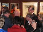 Kansainvälinen presidentti Joe Preston (vas.) kiinnittää lionsmerkkiä Juhani Lavosen (kesk.) rintapieleen.