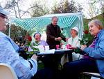 Floorankentän Harri Pirkkalainen ojentamassa äitienpäiväruusuja LC Parkin järjestämässä ulkoilmajuhlassa.