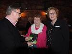 """Kiitokseksi vierailukutsusta Ulla Welin ojensi kirjoittamansa runokirjan """"Siiven hipaisu"""" presidentti Pertti Huoviselle.  Oikealla Malmittarien presidentti Kirsi Sjöblom."""