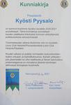 Klubin myöntämä kunniakirja presidentti Kyösti Pyysalolle. Kun-niakirjan on suunnitellut LC Hki/Pasilan kokoussihteeri Jaakko Koskinen.
