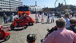 Epätieteilijöiden puheen ja toiminnan johtaja Jaakko Koskinen toivotti yleisön tervetulleeksi kylmän kiven heittotapahtumaan Jaakon päivänä 2021. Kuvassa vasemmalla paikalle etukäteen saapunut palokalusto: taustalla Lauttasaaren VPK:n yksi paloauto, Fiat 500-apusammutusyksikkö ja kaksi palo-Vespaa.