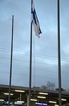 Itsenäisen Suomen lippu heikossa aamutuulen vireessä Martinlaakson asemalla.