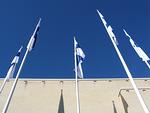 Satavuotiaan itsenäisen Suomen liput taivaan sinessä.