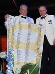 Kuvernööri Aarne Kivioja luovutti seuraajalleen Timo Auraselle satavuotislipun satoine nimikirjoituksineen Chicagon Conventioniin vietäväksi.