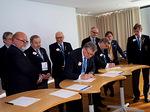 Liiton puheenjohtaja Erkki Honkala allekirjoittamassa haastetta, kuvernöörit odottavat vuoroaan.